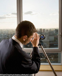 Rear view of a man peering through a telescope out the window from his high rise office. Picture is taken from behind the man. Man wearing business suit and observing the city below through a telescope mounted on a tripod.